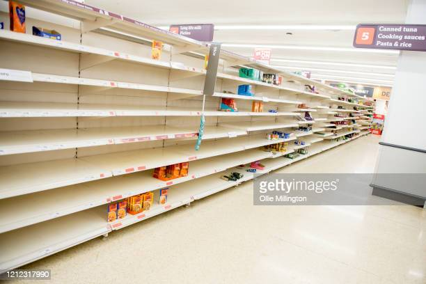 Empty Supermarket shelves are seen along the pasta and rice aisle in a Sainsbury's Superstore shortly after opening at 6am in London as the British...
