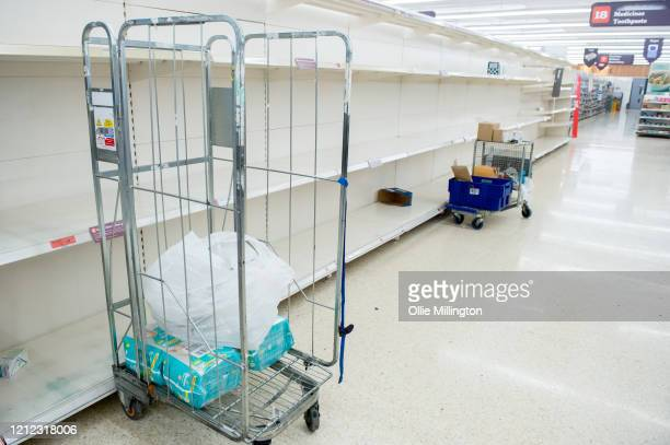 Empty Supermarket toilet roll shleves are seen along the medicine and toothpaste aisle are seen in a Sainsbury's Superstore shortly after opening at...