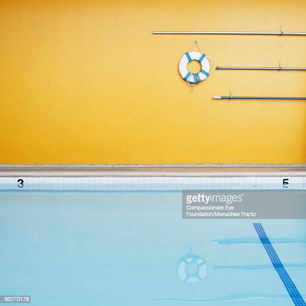 Empty swimming pool, floatation device on wall.