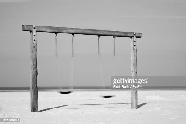 Empty Swing On Beach Against Sky