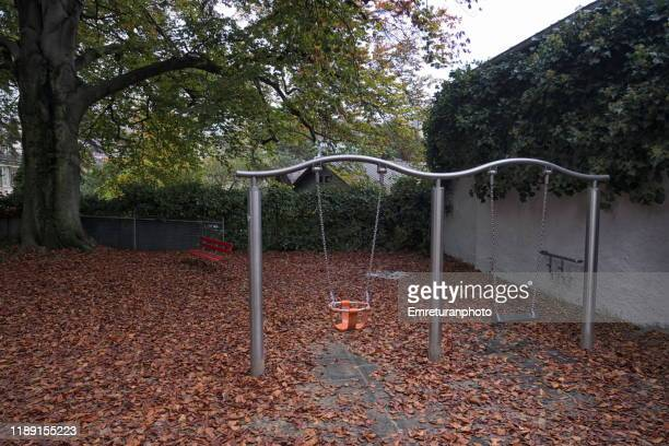 empty swings in a childrens' playground in zurich. - emreturanphoto stock pictures, royalty-free photos & images
