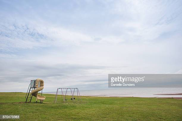 empty swingset and slide at the seashore - moody sky stock pictures, royalty-free photos & images