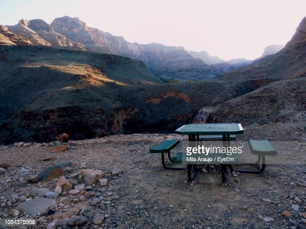 Empty Table And Bench On Mountains Against Sky