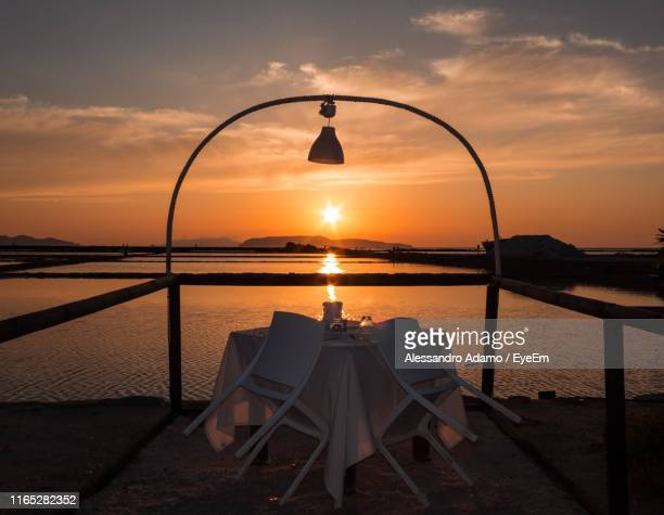 empty table and chairs by sea against sky during sunset - adamo photos et images de collection