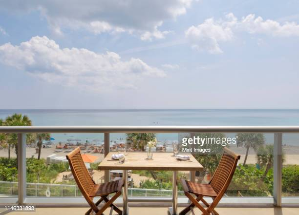 empty table on restaurant balcony overlooking beach - southeast stock pictures, royalty-free photos & images
