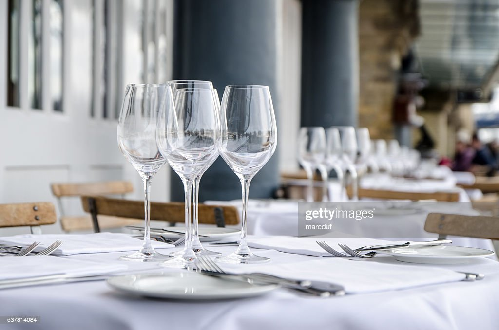 Empty table seen from side on terrace of restaurant : Stock Photo