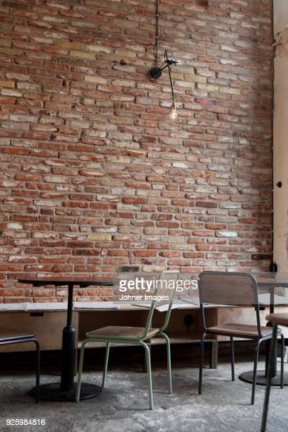 Empty tables and chairs against brick wall