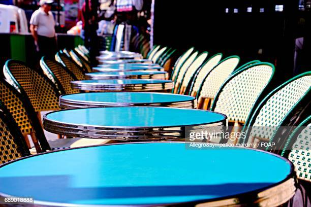 empty tables and chairs arranged in cafe
