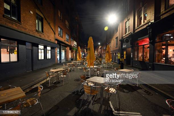 Empty tables and chairs at an outdoor eating area in the city centre of Manchester, north west England on October 8, 2020. - Pubs and restaurants in...