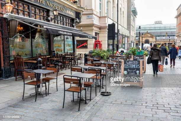 Empty tables are seen outside the The Nags Head pub. The pub has placed a chalk board outside with writings Wanted Customers, buy a pint today to...