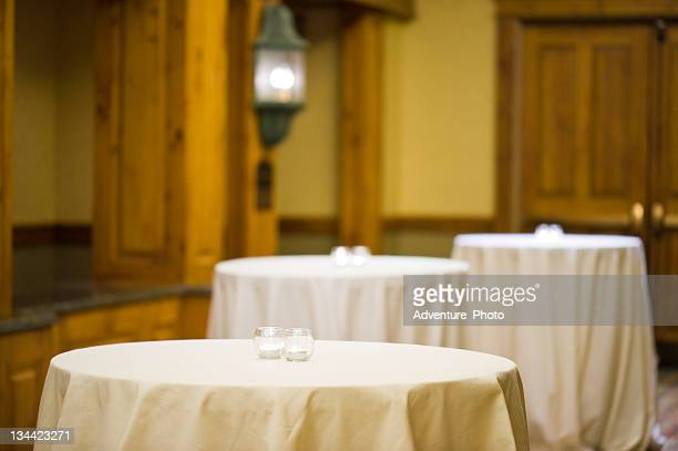 empty tables with tablecloths and burning candles - banquet hall stock pictures, royalty-free photos & images