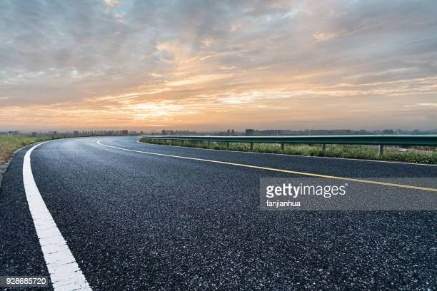 empty tarmac road against sunset sky - curve stock pictures, royalty-free photos & images