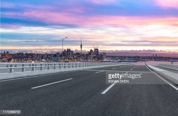 empty tarmac road against sunset urban auckland city - auckland stock pictures, royalty-free photos & images