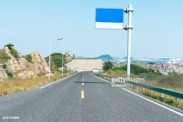 empty tarmac road near by industrial harbor - billboard highway stock pictures, royalty-free photos & images