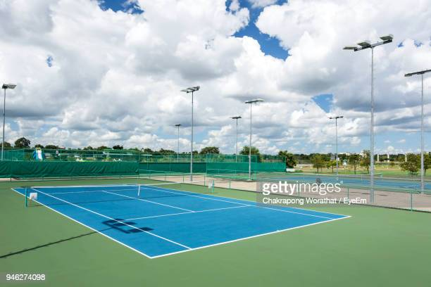 empty tennis court against cloudy sky - tennis stock pictures, royalty-free photos & images