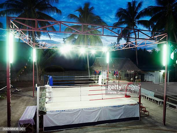 Empty Thai boxing ring illuminated at evening