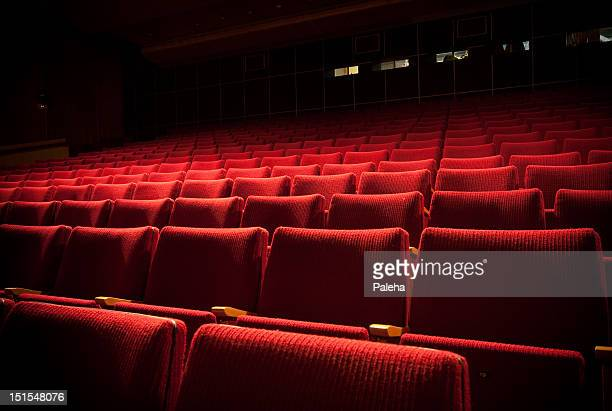 empty theatre with red seats in low light - seat stock pictures, royalty-free photos & images