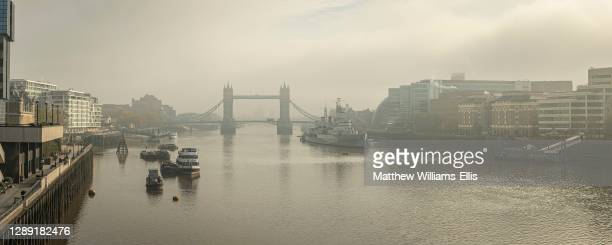 Empty Tower Bridge without traffic in Coronavirus Covid-19 Lockdown in London in foggy misty weather, with the River Thames in beautiful mysterious...