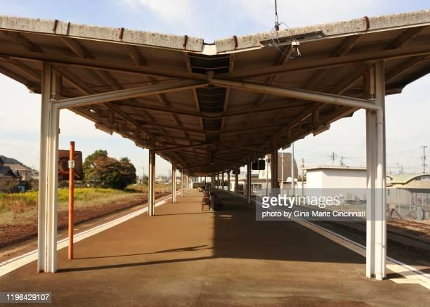 empty train station platform in rural japanese town with half shadow - 鉄道のプラットホーム ストックフォトと画像
