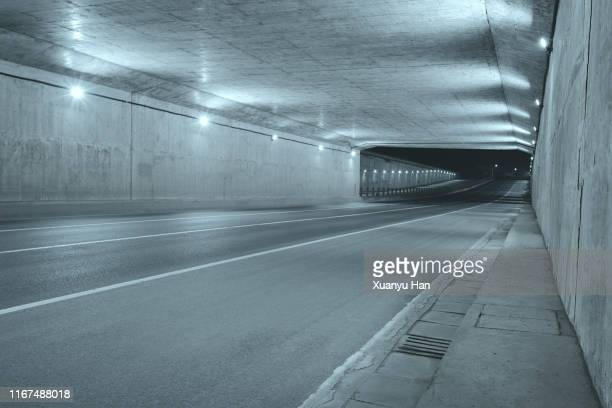 empty tunnel at night - 人気のない道路 ストックフォトと画像