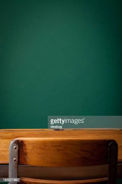Empty Vintage School Desk in Front of Green Chalkboard