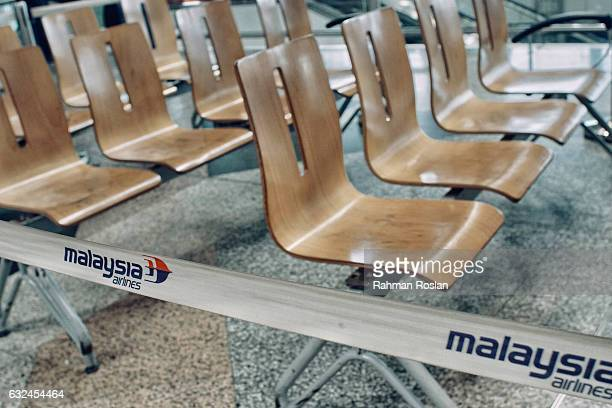 Empty waiting chairs in front of the ticketing counter of Malaysian Airlines at the busy terminal of Kuala Lumpur International airport on January 23...