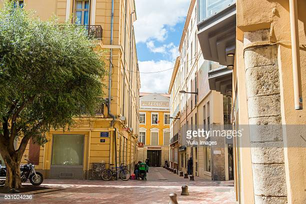 empty walkway between yellow buildings near plaza - perpignan stock photos and pictures