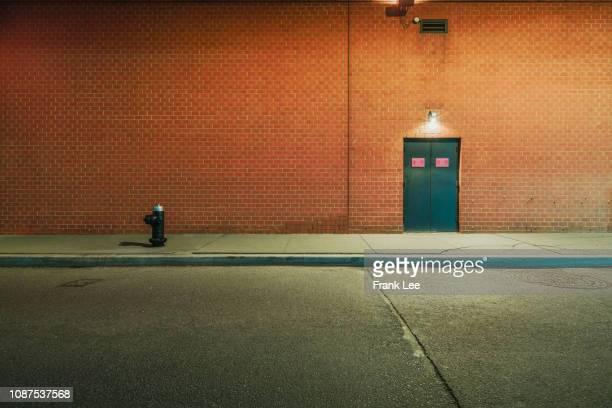 empty wall at night - ziegel stock-fotos und bilder