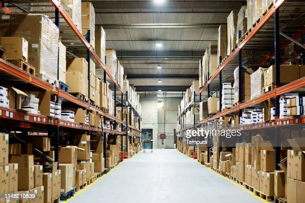 empty warehouse, view down the asile with shelves and boxes. - warehouse stock pictures, royalty-free photos & images