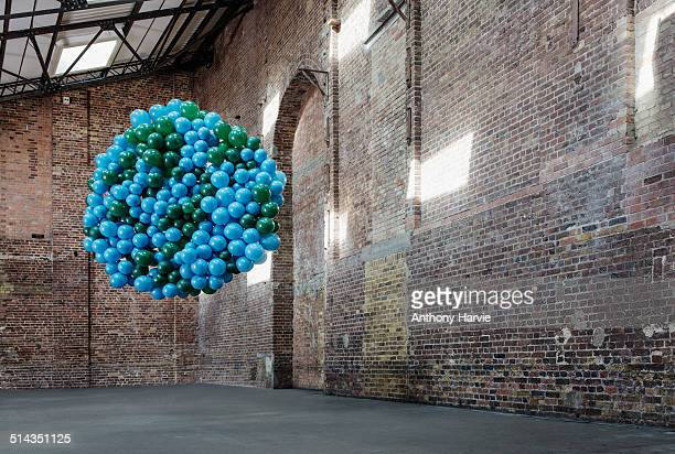 Empty warehouse with globe made of balloons