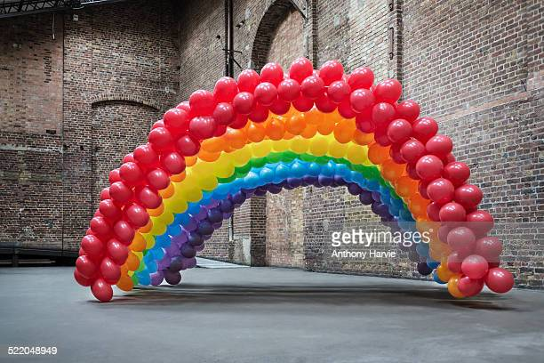 Empty warehouse with rainbow made of balloons