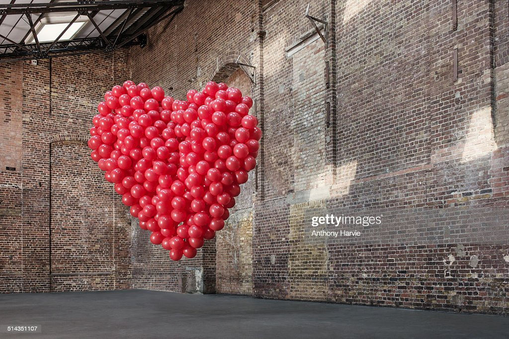 Empty warehouse with red heart made of balloons : Stock Photo