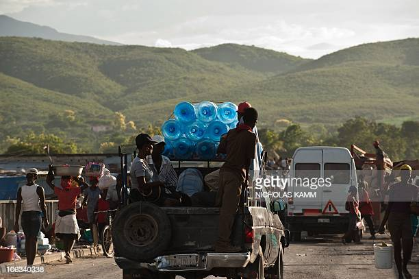Empty water containers are transported on the back of a pickup truck at the weekly market on a bridge over the Artibonite river whose waters are...