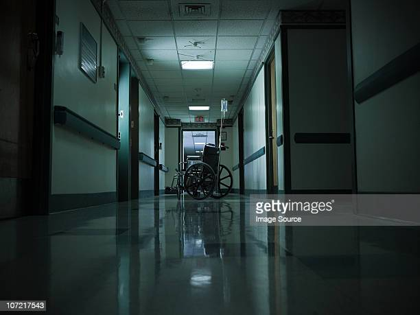 empty wheelchair and intravenous drip in hospital corridor - abandoned stock pictures, royalty-free photos & images