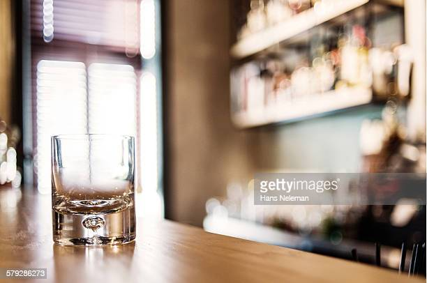 Empty whisky glass on wooden bar