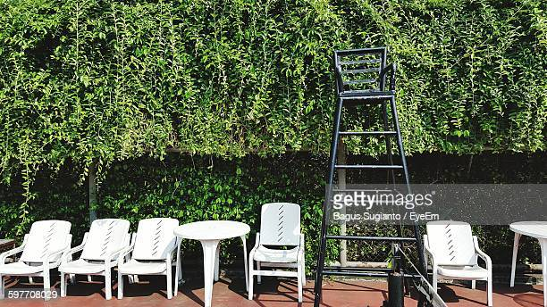 Empty White Chairs Against Plants At Tennis Court