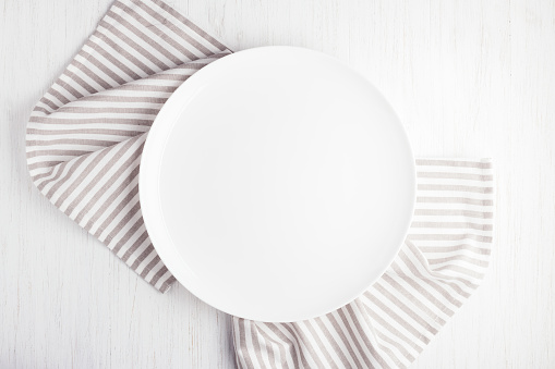 Empty white circle plate on wooden table 984688858