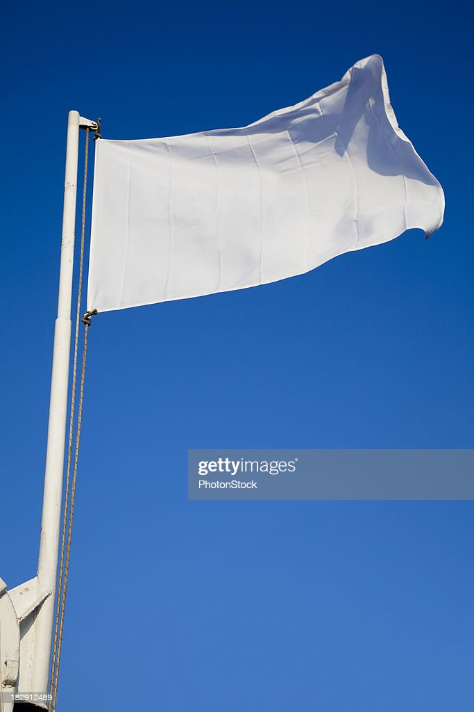 Empty white flag waves in front of deep blue sky : Stock Photo