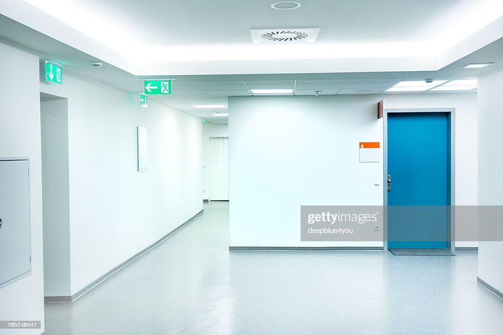 Empty white Hospital corridor with a blue door : Stock Photo