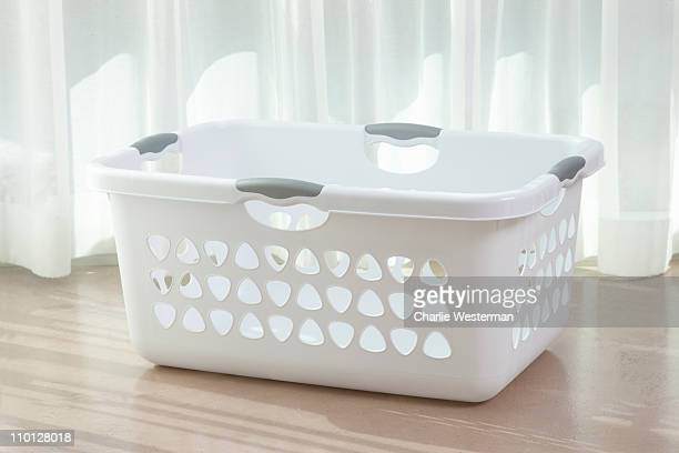 Empty white laundry basket on floor.