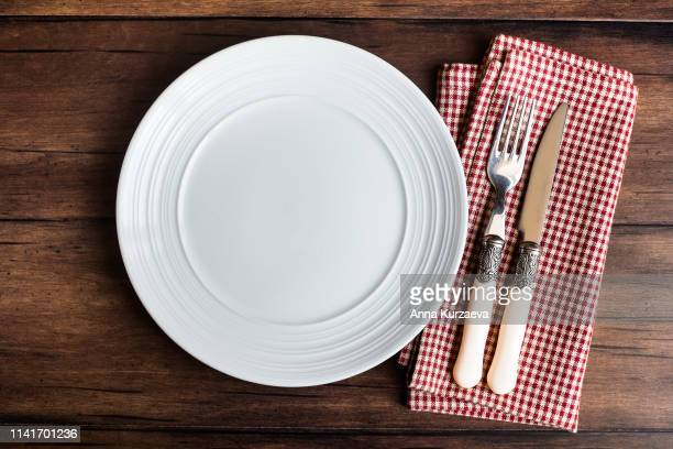 Empty white plate, fork and knife on a napkin on an old wooden brown background, top view. Image with copy space. Kitchen table with a towel and a plate - top view with copy space.