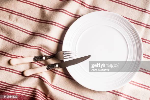 Empty white plate, fork and knife on a red and white linen striped napkin, top view. Image with copy space. Kitchen table with a towel and a plate - top view with copy space.
