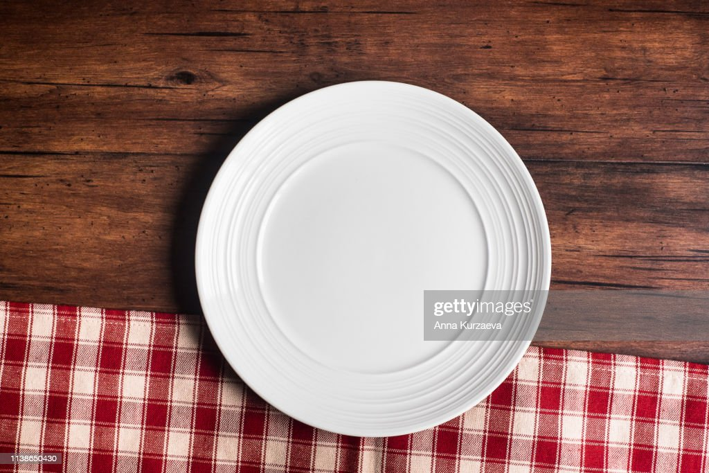 Empty white plate on a napkin on an old wooden brown background, top view. Image with copy space. Kitchen table with a towel and a plate - top view with copy space. : Stock Photo