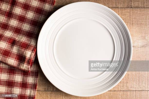 empty white plate on a red and white checkered napkin, top view. image with copy space. kitchen table with a towel and a plate - top view with copy space. - fasting activity stock pictures, royalty-free photos & images