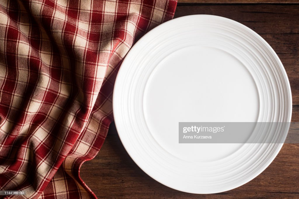 Empty white plate with a napkin on an old wooden brown background, top view. Image with copy space. Kitchen table with a towel and a plate - top view with copy space. : Stock Photo