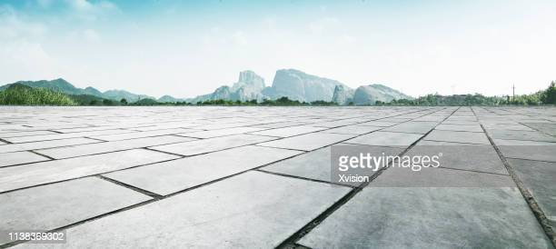 empty wide open marble pavement for automobile commercial with rock mountain in the background - physical structure stock pictures, royalty-free photos & images