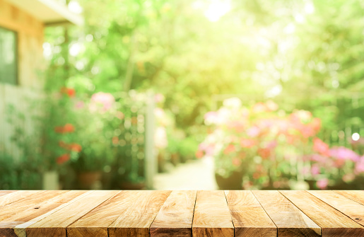 Empty wood table top on blur abstract green from garden and house background 928765222