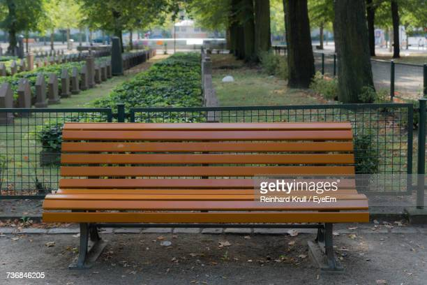 Empty Wooden Bench At Cemetery