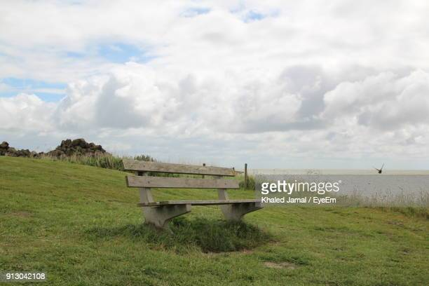 Empty Wooden Bench On Grass Against Cloudy Sky