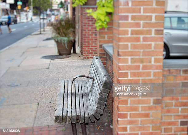 empty wooden bench on sidewalk in city - eileen kirsch stock pictures, royalty-free photos & images